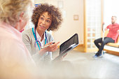 female-doctor-sits-in-a-medical-clinic-chatting-with-senior-patient