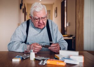 elderly-man-looking-at-his-prescription-medications-in-his-home-at-a-table