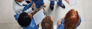 team-of-healthcare-providers-in-scrubs-talking-in-a-circle