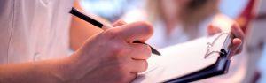 caucasian-male-writing-on-clipboard