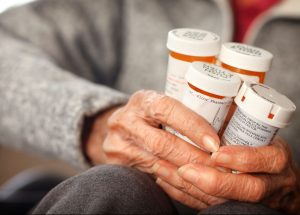 hands-of-an-elderly-woman-holding-prescription-medication-bottles