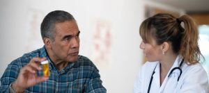 hispanic-male-patient-discussing-prescription-medication-with-female-doctor