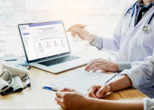 doctors-looking-at-a-laptop-screen-with-the-cmm-implementation-system-overview-page