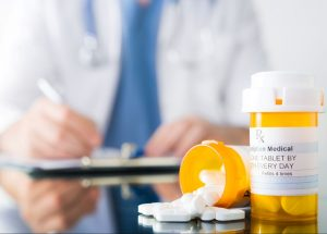 male-doctor-writing-on-a-clipboard-beside-prescription-medication-bottles