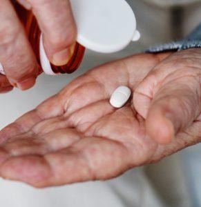 elderly-person-pouring-white-pill-out-of-prescription-bottle