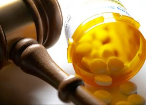 open-prescription-medication-bottle-next-to-a-gavel
