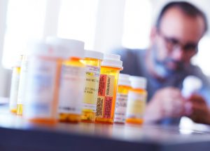 male-patient-with-many-medication-prescription-bottles